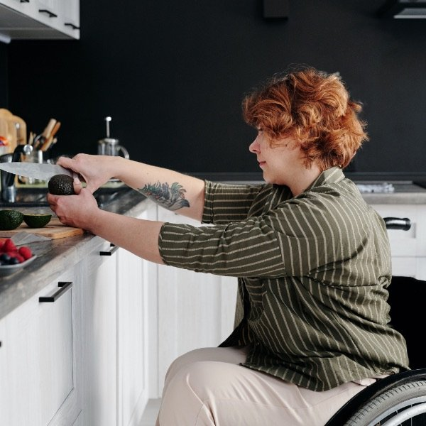 Woman in wheelchair cooking