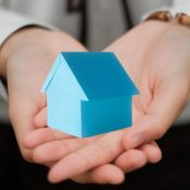 Hands holding blue house
